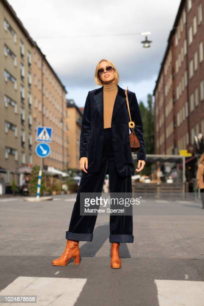 A guest is seen on the street during Fashion Week Stockholm wearing a navy velvet suit with tan sweater and carmel leather boots on August 28 2018 in...