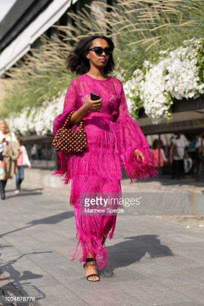 A guest is seen on the street during Fashion Week Stockholm wearing a pink fringe dress with wooden bead bag on August 28 2018 in Stockholm Sweden
