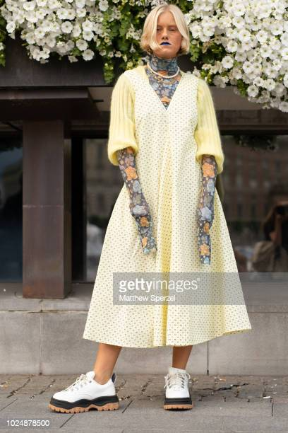 A guest is seen on the street during Fashion Week Stockholm wearing cream dress with yellow sweater floral oversized turtleneck and white sneakers on...