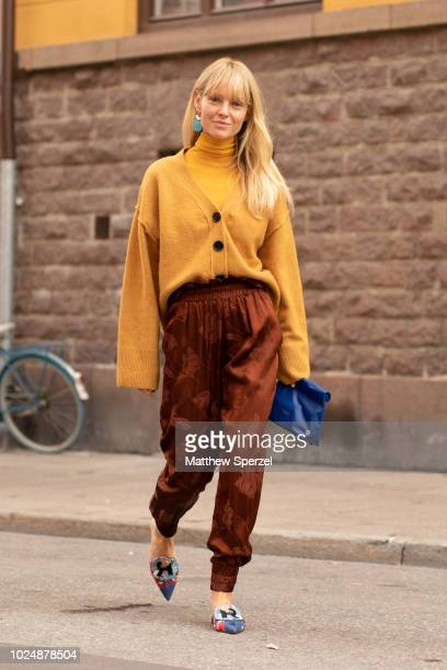 A guest is seen on the street during Fashion Week Stockholm wearing gold sweater yellow turtleneck satin floral copper pants and blue bag on August...