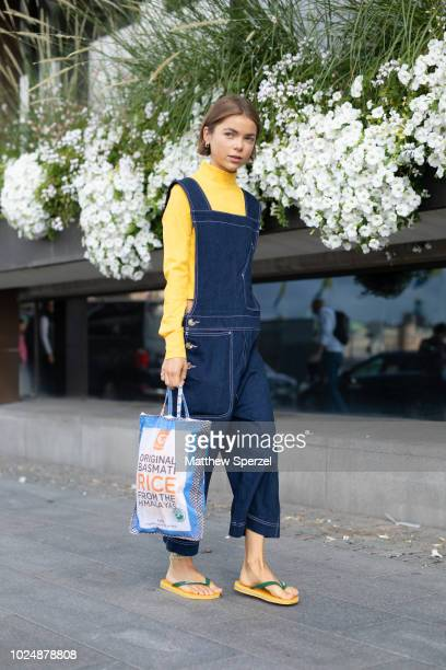 A guest is seen on the street during Fashion Week Stockholm wearing blue overalls with yellow turtleneck and sandals on August 28 2018 in Stockholm...