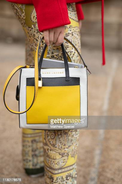A guest is seen on the street during London Fashion Week February 2019 wearing Marc Jacobs bag on February 16 2019 in London England