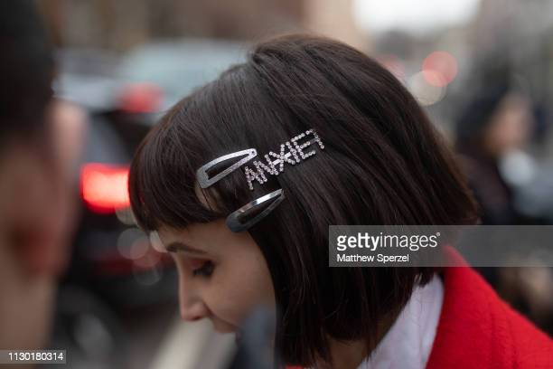 A guest is seen on the street during London Fashion Week February 2019 wearing 'Anxiety' barrette on February 16 2019 in London England