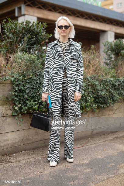 A guest is seen on the street during London Fashion Week February 2019 wearing zebra print coat shirt and pants with black hand bag on February 16...