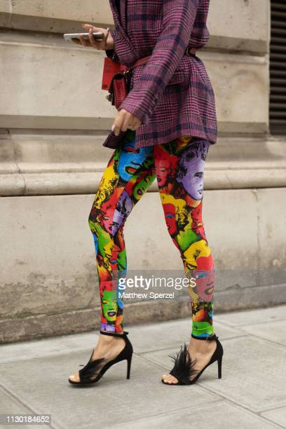 A guest is seen on the street during London Fashion Week February 2019 wearing rainbow Marilyn Monroe print leggings with black heels on February 16...