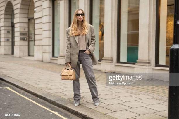 A guest is seen on the street during London Fashion Week February 2019 wearing taupe blazer and sweater with grey pants and tan bag on February 16...