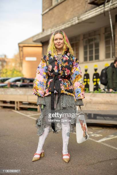 A guest is seen on the street during London Fashion Week February 2019 wearing multi color floral coat with black stripe layered skirt and black bow...