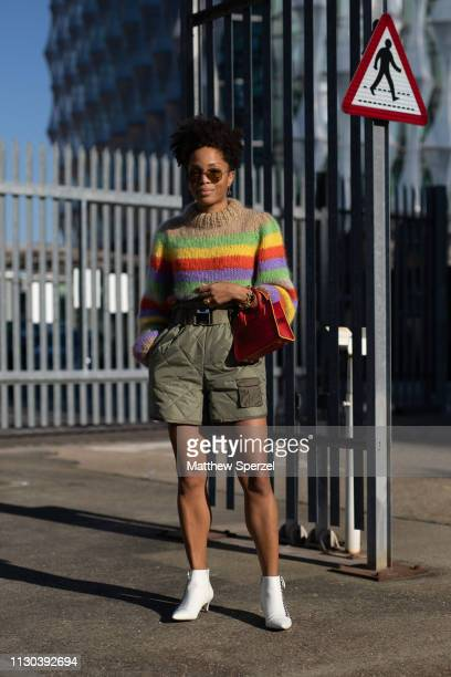 A guest is seen on the street during London Fashion Week February 2019 wearing rainbow sweater with army green quilted shorts and red hand bag on...