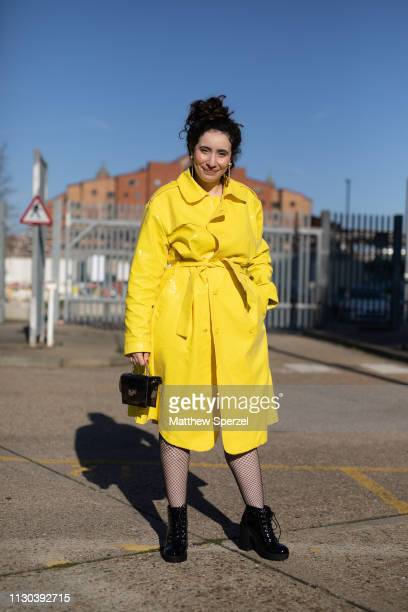 A guest is seen on the street during London Fashion Week February 2019 wearing yellow coat on February 17 2019 in London England