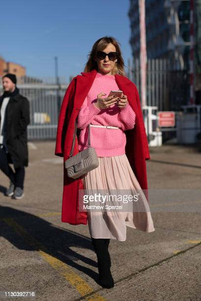 Guest is seen on the street during London Fashion Week February 2019 wearing red coat, pink sweater and nude pleated skirt with grey bag on February...