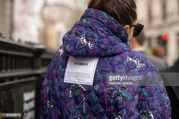 A guest is seen on the street during London Fashion Week February 2019 wearing Vetements purple pattern quilted coat on February 18 2019 in London...