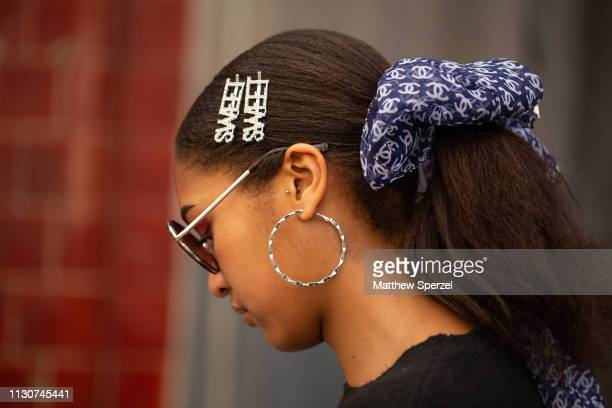 A guest is seen on the street during London Fashion Week February 2019 wearing navy Chanel hair bow with two 'Sweet' barrettes on February 19 2019 in...