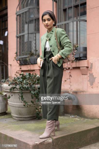 A guest is seen on the street during Men's Fashion Week New York wearing maroon hijab green jacket dark green pants and white shirt with shoulder bag...