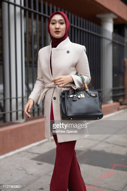 A guest is seen on the street during Men's Fashion Week New York wearing merlot hijab and pants with cream wool coat and black hand bag on February...