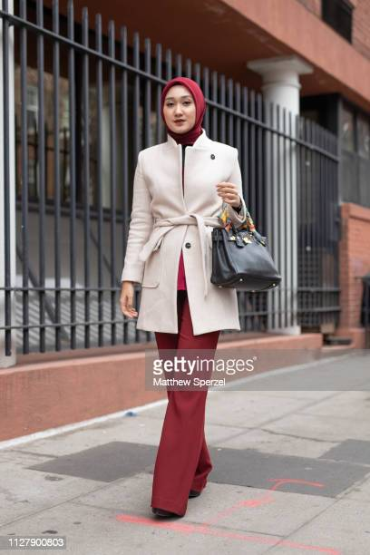 Guest is seen on the street during Men's Fashion Week New York wearing merlot hijab and pants with cream wool coat and black hand bag on February 06,...