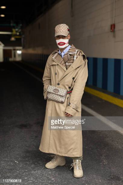 Guest is seen on the street during Men's Fashion Week New York wearing khaki trench coat, Gucci hip belt bag and hat, GCDS face mask and khaki boots...