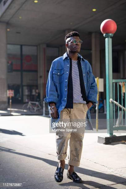 A guest is seen on the street during Men's New York Fashion Week wearing blue denim shirt khaki pants on February 05 2019 in New York City