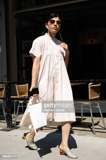 A guest is seen on the street during Men's New York Fashion Week wearing a cream dress with grey heels on July 11 2018 in New York City