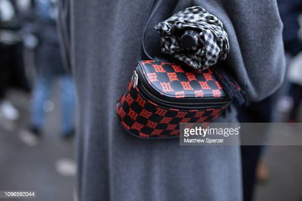 A guest is seen on the street during Men's Paris Fashion Week AW19 wearing red/black bag on January 19 2019 in Paris France