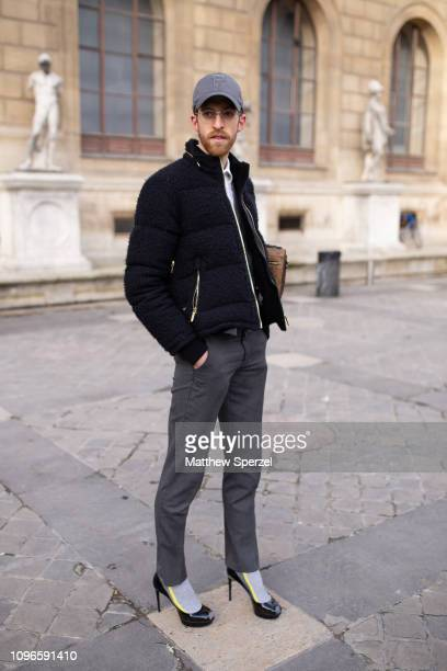 A guest is seen on the street during Men's Paris Fashion Week AW19 wearing grey cap black/white jacket Louis Vuitton bag grey slacks and heels on...
