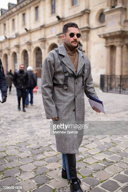 A guest is seen on the street during Men's Paris Fashion Week AW19 wearing grey wool coat with black chest harness on January 19 2019 in Paris France