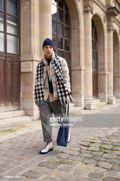 A guest is seen on the street during Men's Paris Fashion Week AW19 wearing navy beanie black/white checker scarf taupe down coat black plaid pants on...