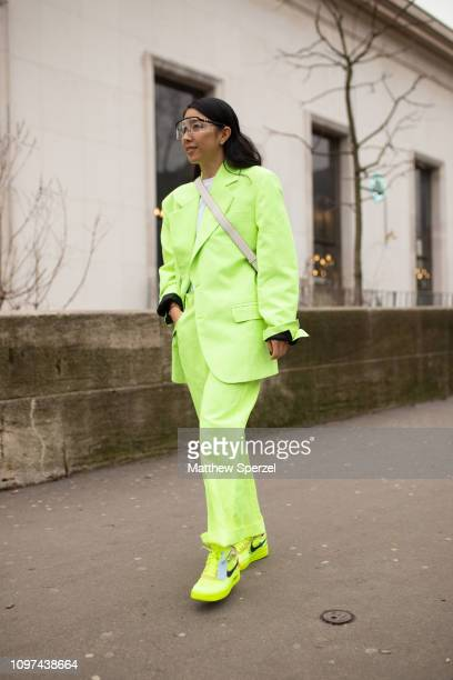 A guest is seen on the street during Men's Paris Fashion Week AW19 wearing neon suit and Nike sneakers on January 20 2019 in Paris France