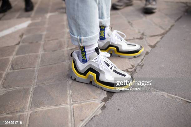 A guest is seen on the street during Men's Paris Fashion Week AW19 wearing grey/yellow/black/white sneakers on January 19 2019 in Paris France