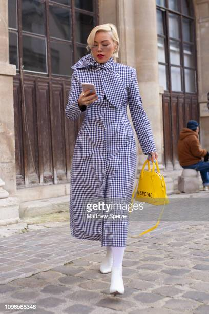 A guest is seen on the street during Men's Paris Fashion Week AW19 wearing blue/white checker coat with yellow Balenciaga bag and white shoes on...
