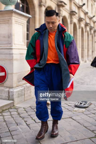 A guest is seen on the street during Men's Paris Fashion Week AW19 wearing orange Heron Preston shirt colorful ski jacket blue pants and brown shoes...
