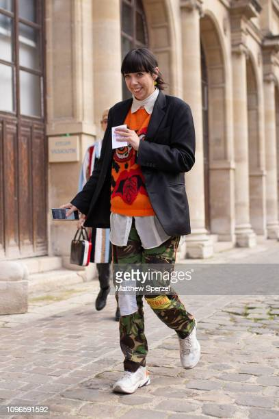 A guest is seen on the street during Men's Paris Fashion Week AW19 wearing black blazer orange sweater camo pants and white sneakers on January 19...