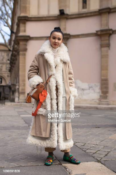 A guest is seen on the street during Men's Paris Fashion Week AW19 wearing taupe shearling coat brown/orange leather shoulder bag colorful shoes on...