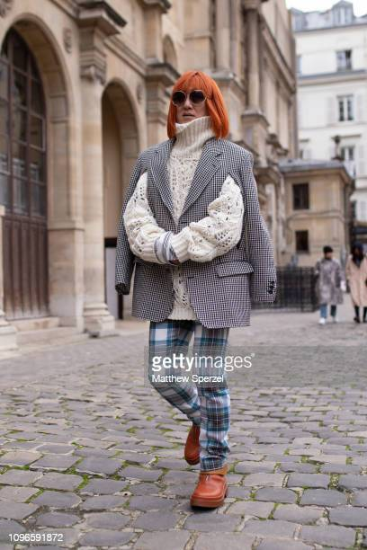 A guest is seen on the street during Men's Paris Fashion Week AW19 wearing cream knit sweater houndstooth jacket blue plaid pants tan leather shoes...