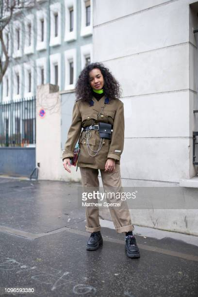 A guest is seen on the street during Men's Paris Fashion Week AW19 wearing khaki slacks black shoes military jacket black leather belt and pocket...