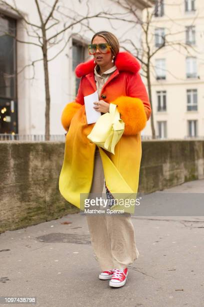 A guest is seen on the street during Men's Paris Fashion Week AW19 wearing red/orange/yellow coat with khaki pants and pink sneakers on January 20...