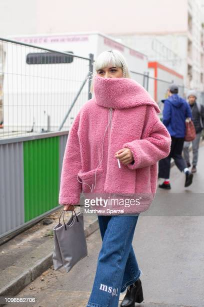 A guest is seen on the street during Men's Paris Fashion Week AW19 wearing pink fleece coat with grey handbag on January 19 2019 in Paris France