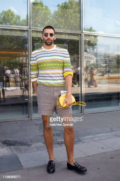 A guest is seen on the street during men's Paris Fashion Week wearing cream/blue/yellow striped sweater gray shorts black loafers and yellow bag on...