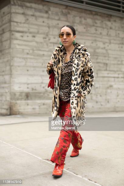 A guest is seen on the street during New York Fashion Week AW19 wearing leopard print fur coat and shirt with red pattern pants and shoes on February...