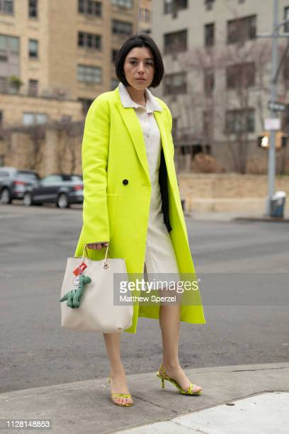 A guest is seen on the street during New York Fashion Week AW19 wearing neon yellow coat taupe dress and bag on February 07 2019 in New York City