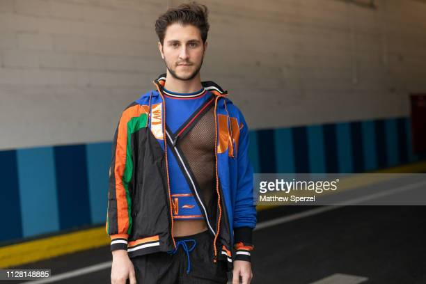 A guest is seen on the street during New York Fashion Week AW19 wearing blue/orange jacket and shirt with black track pants on February 07 2019 in...