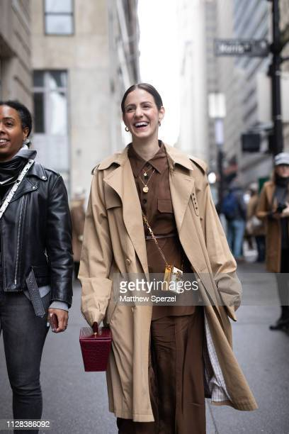 A guest is seen on the street during New York Fashion Week AW19 wearing khaki trench coat with brown dress on February 08 2019 in New York City