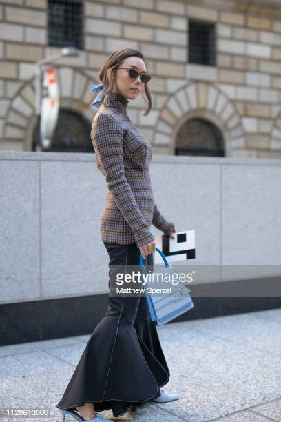 A guest is seen on the street during New York Fashion Week AW19 wearing grey sweater black pants and baby blue hand bag shoes and hair bow on...