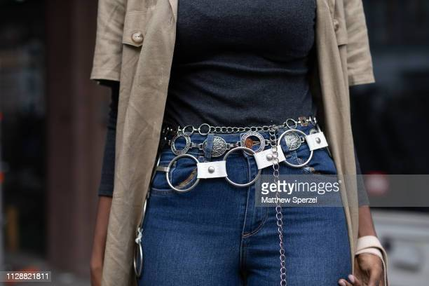 A guest is seen on the street during New York Fashion Week AW19 wearing multiple silver chain belts on February 10 2019 in New York City