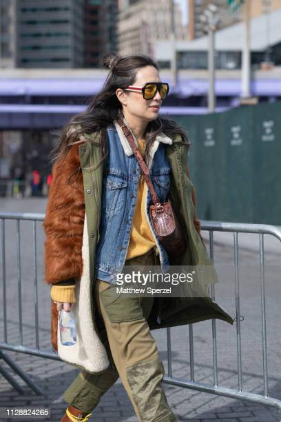 A guest is seen on the street during New York Fashion Week AW19 wearing brown fur with army green coat denim jacket cargo pants and shoulder bag on...