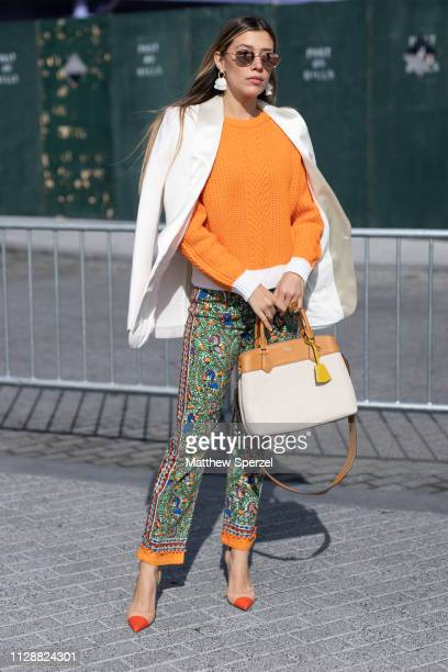 A guest is seen on the street during New York Fashion Week AW19 wearing orange sweater white blazer Tory Burch pants on February 10 2019 in New York...