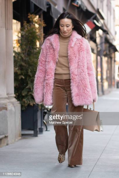 Guest is seen on the street during New York Fashion Week AW19 wearing pink fur coat with nude sweater and brown velvet pants on February 10, 2019 in...
