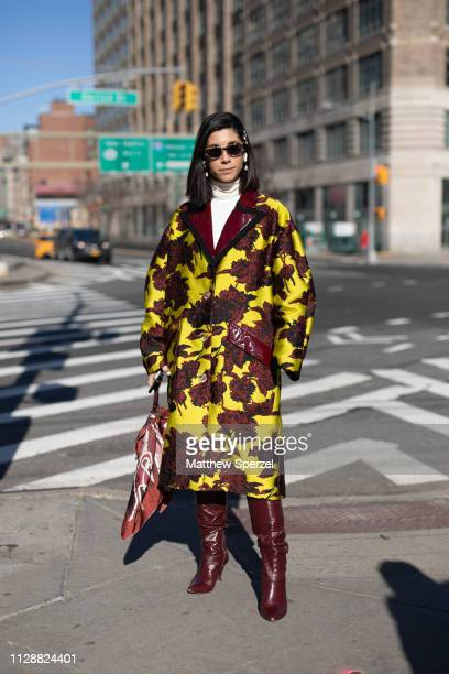 Guest is seen on the street during New York Fashion Week AW19 wearing yellow/maroon pattern coat with maroon boots on February 10, 2019 in New York...