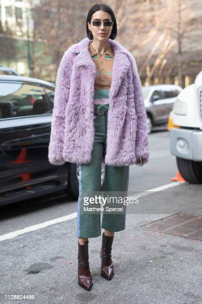 A guest is seen on the street during New York Fashion Week AW19 wearing purple fur coat sea green pants on February 10 2019 in New York City