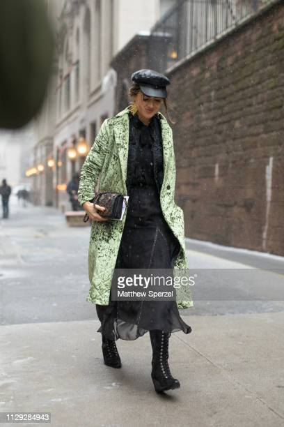 Guest is seen on the street during New York Fashion Week AW19 wearing green Coach coat with black dress and cap on February 12, 2019 in New York City.
