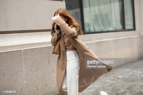 A guest is seen on the street during New York Fashion Week AW19 wearing camel wool coat with white pants on February 12 2019 in New York City